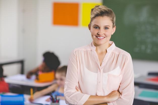 Professor de pé com os braços cruzados na sala de aula