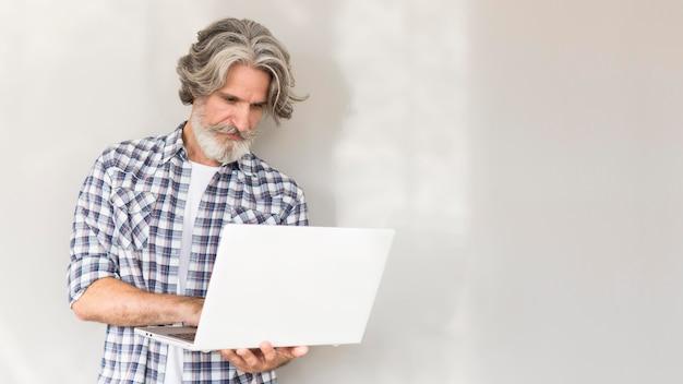 Professor de pé e segurando laptop