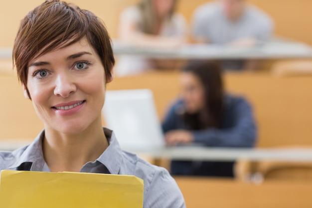 Professor de pé na sala de aula sorrindo