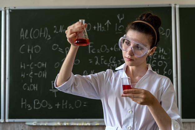 Professor de química examina frasco cônico com líquido de cor, aula de explano
