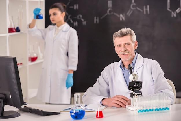 Professor de química sênior e seu assistente trabalhando.