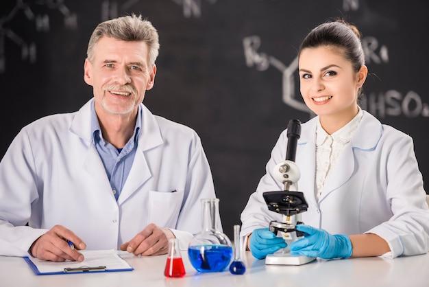 Professor de química sênior e seu trabalho de assistente.