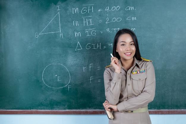 Professor de tailandês com roupa oficial de ensino na frente do encosto