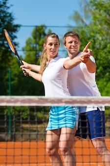 Professor de tênis, ajudando a mulher a jogar