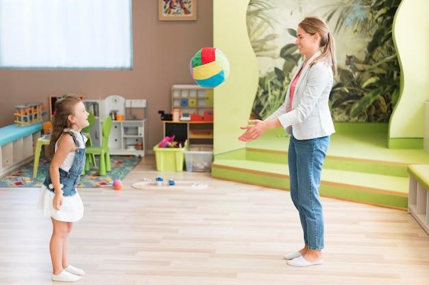 Professor de tiro completo e menina brincando com bola