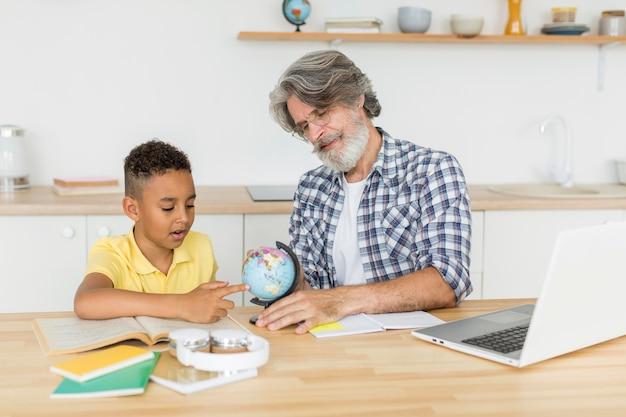 Professor de tiro médio mostrando o globo da terra para aluno