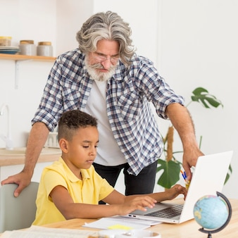 Professor de tiro médio sentado ao lado do aluno no laptop