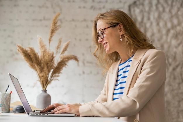 Professor de visão lateral trabalhando em um laptop