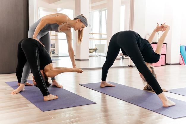 Professor de yoga e iniciante em aula, fazendo exercícios de asana. estilo de vida saudável em clube de fitness
