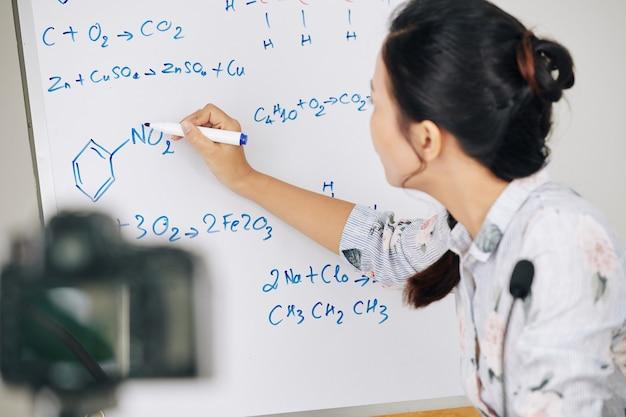 Professor desenhando estrutura química