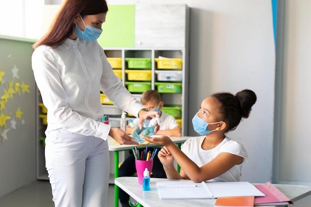 Professor desinfetando mãos de crianças