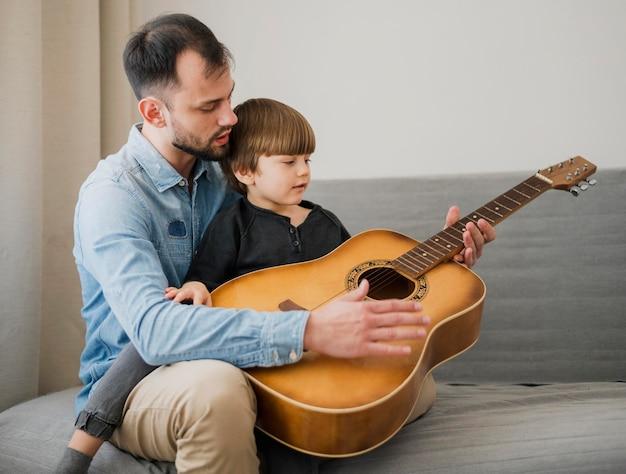 Professor do sexo masculino dando aulas de violão para criança em casa