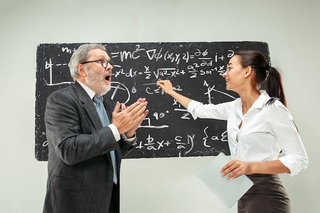 Professor do sexo masculino e jovem mulher contra lousa em sala de aula