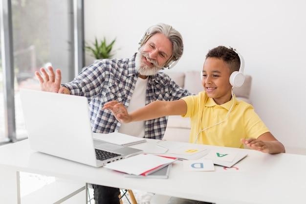 Professor e aluno acenando para laptop