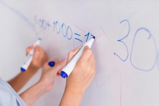 Professor e aluno fazendo cálculos em um quadro branco