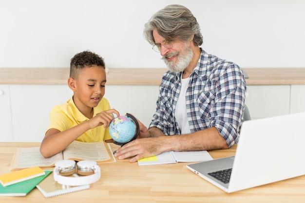 Professor e aluno, olhando para o globo da terra