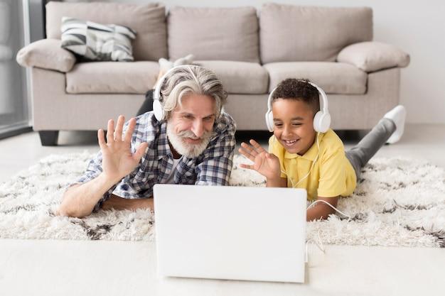 Professor e aluno sentado no chão, acenando para o laptop