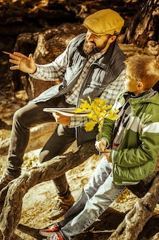 Professor e aluno sentados entre raízes de árvores na floresta dando uma aula em um dia bom