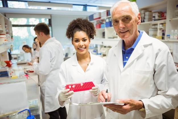 Professor e aluno sorrindo para a câmera no laboratório