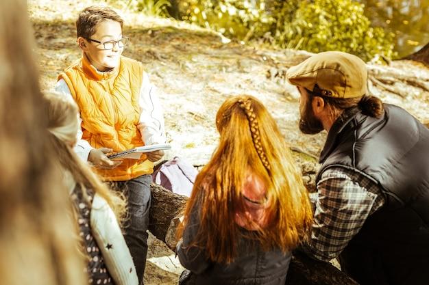Professor e alunos ouvindo um menino falando em um dia bom