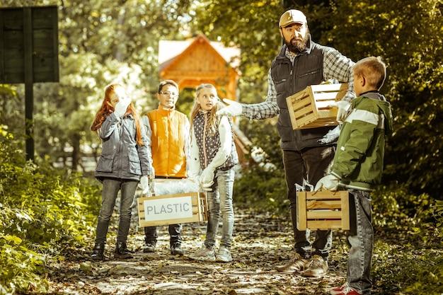 Professor e alunos parados em uma trilha da floresta segurando caixas de lixo classificado em um dia bom