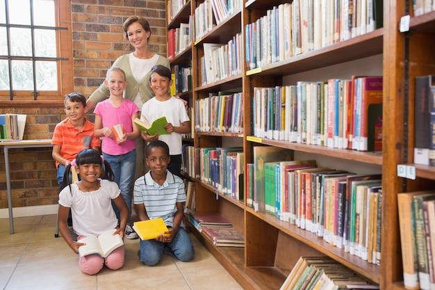 Professor e alunos sorrindo na câmera na biblioteca