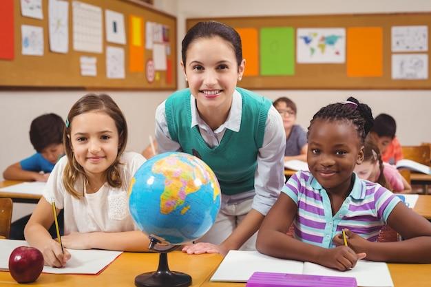 Professor e alunos sorrindo na câmera na sala de aula