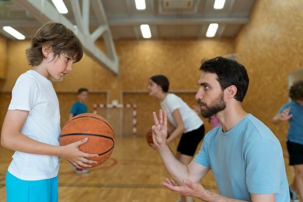 Professor e criança com bola de basquete média tacada