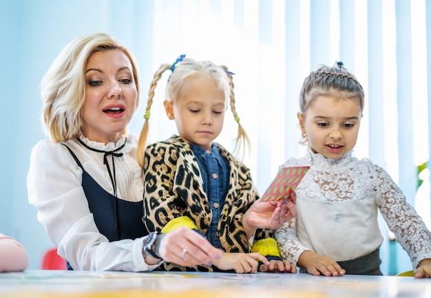 Professor e crianças brincando juntos com cartões coloridos.