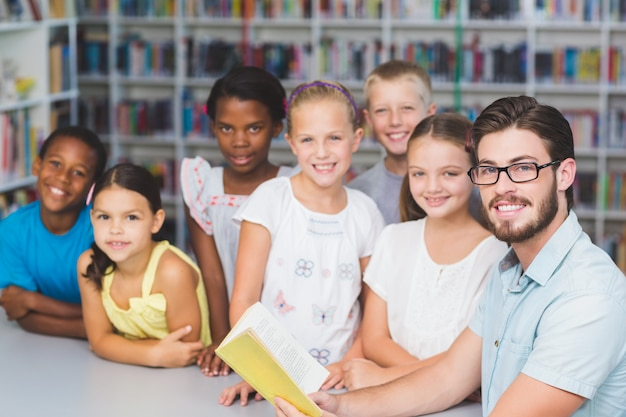 Professor e crianças lendo livro na biblioteca