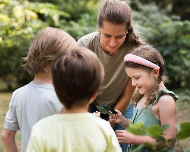 Professor e crianças olhando para as folhas