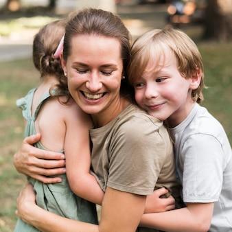 Professor e crianças se abraçando ao ar livre