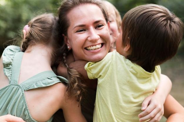 Professor e crianças se abraçando de perto ao ar livre