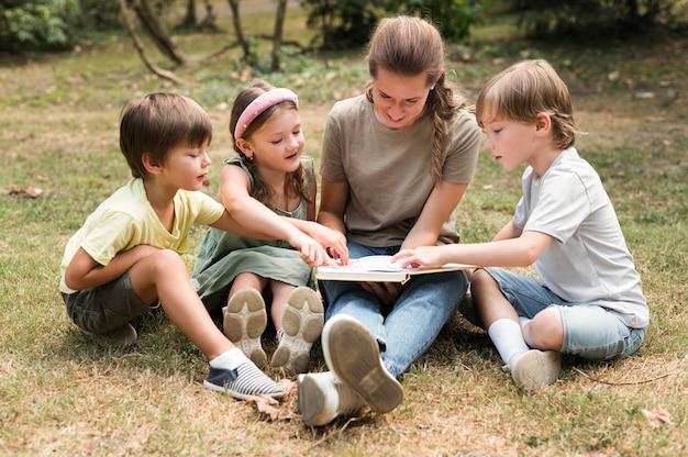 Professor e crianças segurando um livro