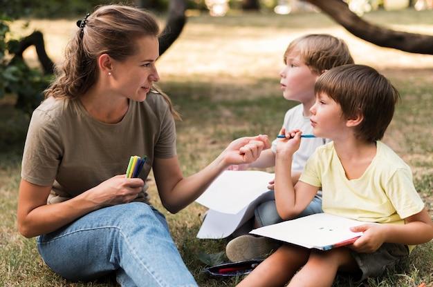 Professor e crianças sentados na grama, tiro médio