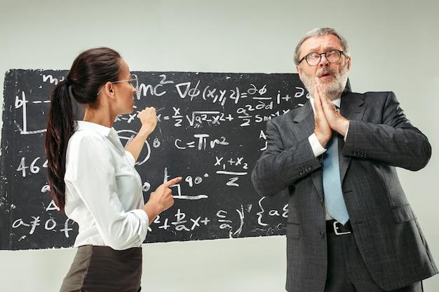 Professor e jovem contra o quadro-negro na sala de aula