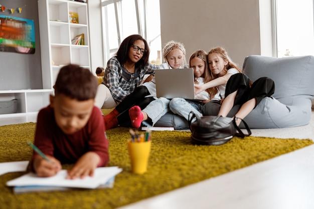 Professor e meninas trabalhando com laptop na aula