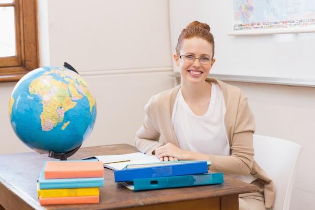 Professor em sala de aula com globo