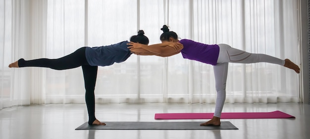 Professor ensina o aluno a fazer o conceito de ioga. uma mulher asiática de meia-idade está ensinando outra mulher a fazer yoga em uma posição de alongamento