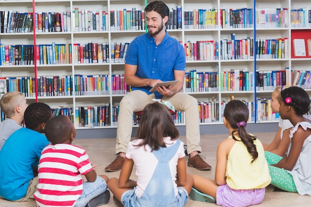 Professor ensinando crianças sobre tablet digital na biblioteca