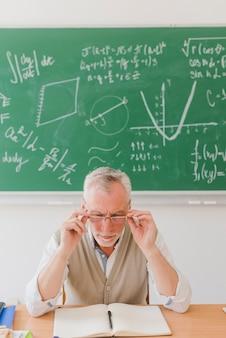 Professor envelhecido, olhando para o caderno com atenção