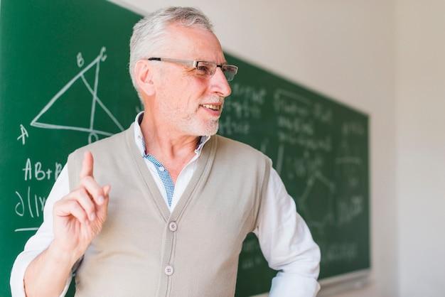 Professor envelhecido palestrando perto de lousa em sala de aula