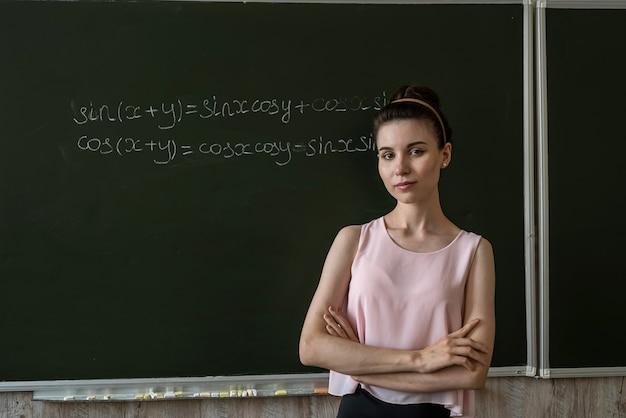 Professor escrito nas fórmulas matemáticas do conselho escolar. álgebra