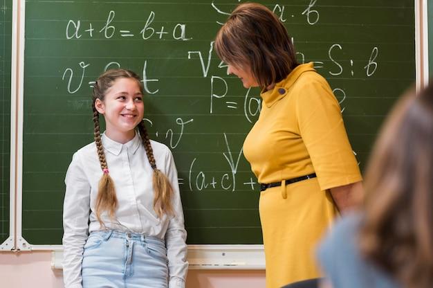 Professor explicando a lição para uma garota na classe