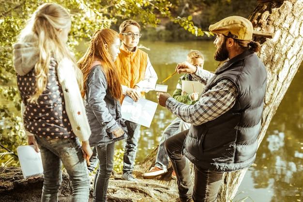Professor explicando questões ecológicas para seus alunos na floresta em um dia bom