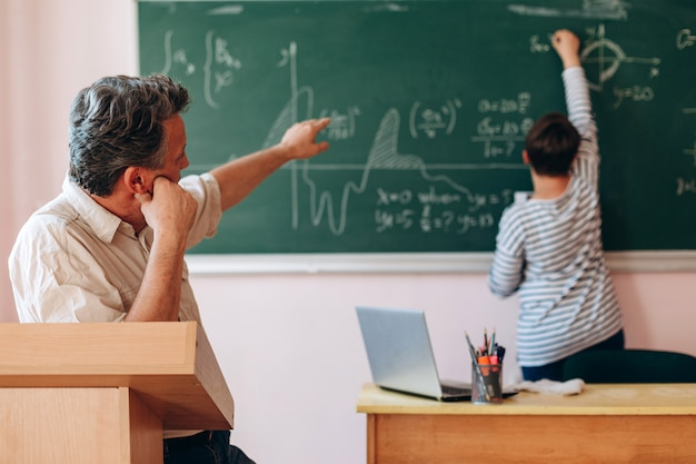 Professor explicar uma lição para o aluno que está ao lado de um quadro negro.