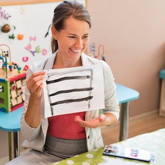 Professor feliz em cena média segurando uma pintura