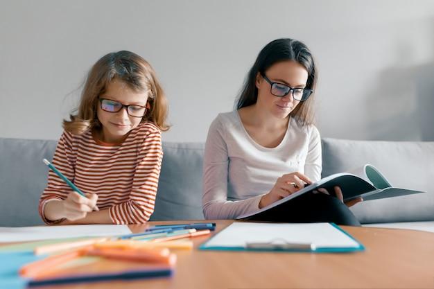 Professor fêmea novo que dá a lição confidencial à criança, menina que senta-se em sua escrita da mesa no caderno.