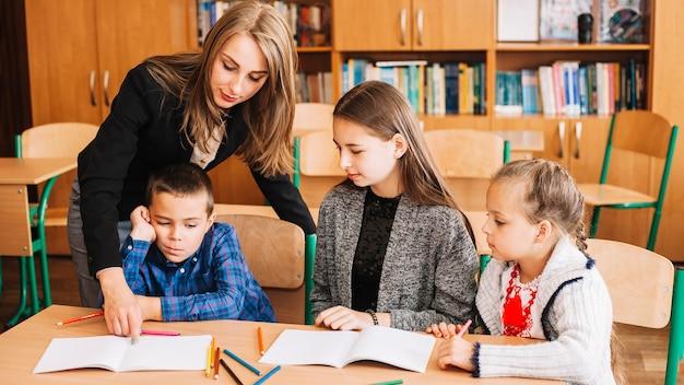 Professor feminino, ajudando, pupilas, em, estudar, processo
