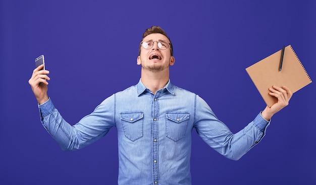Professor ferido com as mãos para cima em copos, camisa jeans azul gritando